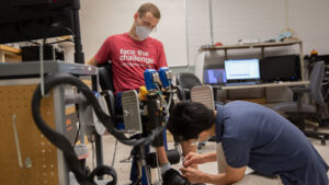 Connor Phillips (left) tests robotic device with his mentor, Assistant Professor Hyunglae Lee
